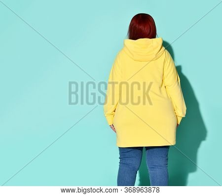 Rear View Of A Voluptuous Lady In Jeans And A Bright Yellow Sweatshirt With A Hood On Her Head. Styl