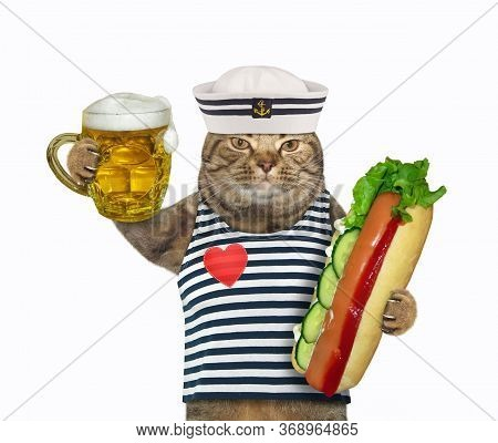 The Beige Cat In Seaman Clothing Is Holding A Mug Of Light Beer And A Big Hot Dog. White Background.