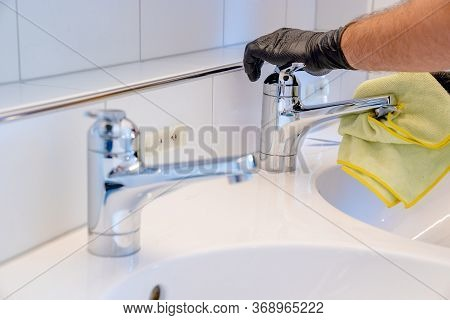 Professional Cleaner Polishes A Bathroom Sink And Faucet With A Yellow Micro Fiber Cloth