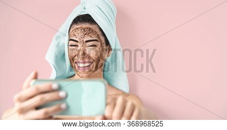 Young Smiling Woman Taking Selfie While Doing Coffee Scrub Facial Mask - Happy Girl Having Skin Care