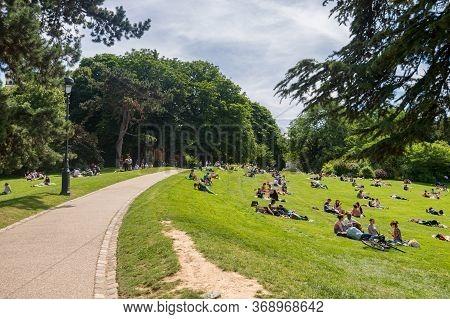 Paris, France - 23 June 2018: People Enjoy Sunny Weather At Parc Des Buttes-chaumont