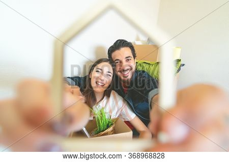 Happy Young Couple Moving In New Home First Time - Man And Woman Having Fun Unpacking Carton Box In