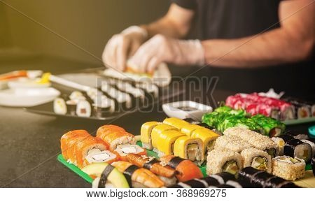 Cook Hands Making Japanese Sushi Roll. Japanese Chef At Work Preparing Delicious Sushi Roll With Eel