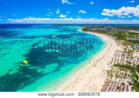 Aerial Drone View Of Beautiful Atlantic Tropical Beach With Palms, Straw Umbrellas And Boats. Bavaro