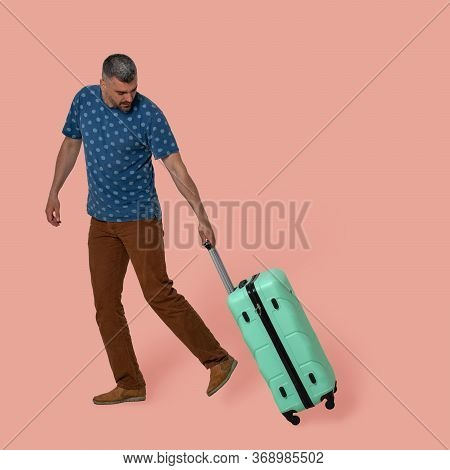 Attractive Man Carries Plastic Suitcase On Wheels Holding It By Telescopic Handle. Young Caucasian T