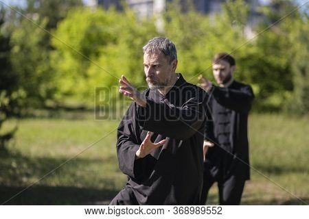 Two Men Practicing Tai Chi Taijiquan In The Park In The Fresh Air