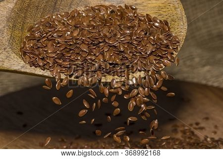 Flax Seeds Pouring End Rotating In Slow Motion. Flax Seeds In A Wooden Spoon.