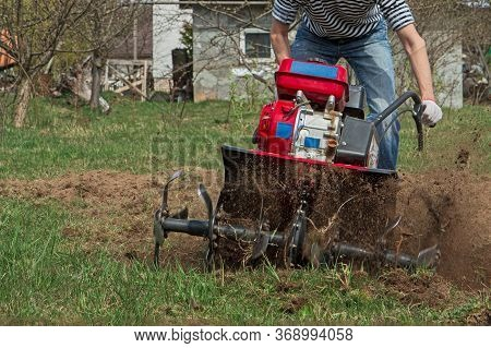 Man Working In The Garden With Garden Tiller. Tractor Cultivating And Loosens Soil Field