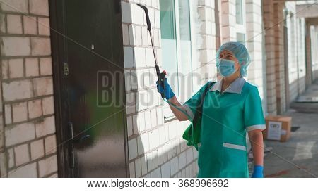 Medical Worker Spraying Antiseptic Spray On Hospital Door And Brick Wall. Treatment Of Building With