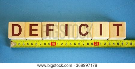 Deficit Word On Cubes Arranged Behind The Ruler On Blue Background.