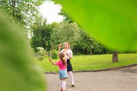 Two Happy Cute Little Sisters Jumping With Colorful Toy Balloon Outdoors. Smiling Kids Having Fun In