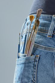 Brushes In The Pocket Of The Girls Jeans On A Gray Background. Artist Painting Concept.