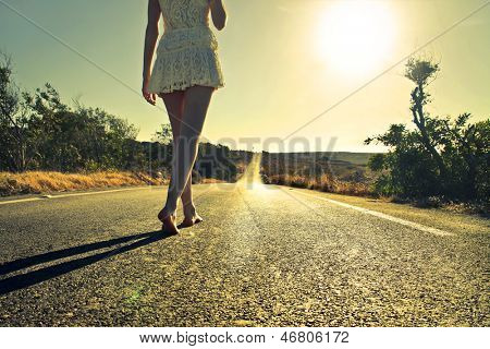 young woman walking barefoot on a long deserted road
