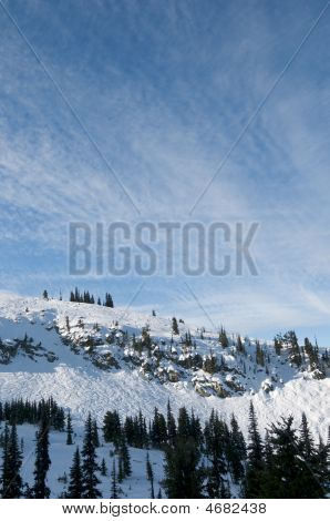 Snow Covered Peak Under Thin Clouds