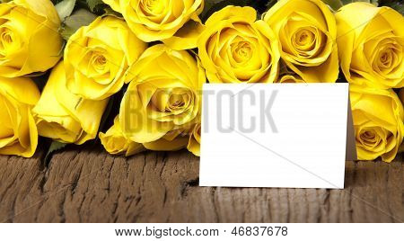 Bouquet of yellow roses with a writable white card on a old wooden board poster