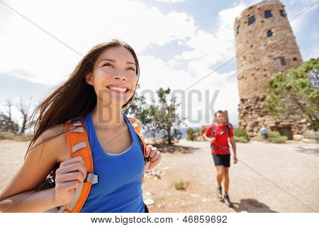 Hiking woman in grand canyon. Female hiker smiling happy with boyfriend in background during hike trekking at South Rim, Desert View Watchtower, Arizona, USA. Couple living healthy liifestyle.