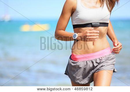 Mulher de corredor com monitor de freqüência cardíaca, correndo na praia com relógio e esportes top sutiã. Lindo apto f