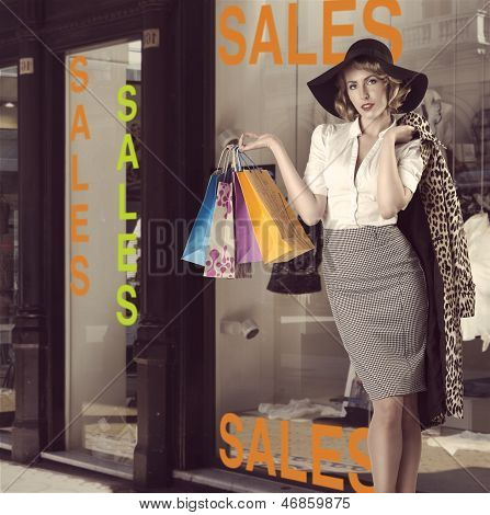 fashion blonde woman posing and taking some colorful shopping bags. She wearing kitsch leopard coat and big black hat in front of window shop poster