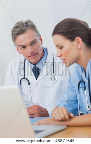 Doctor listening attentively to a colleague in a medical office