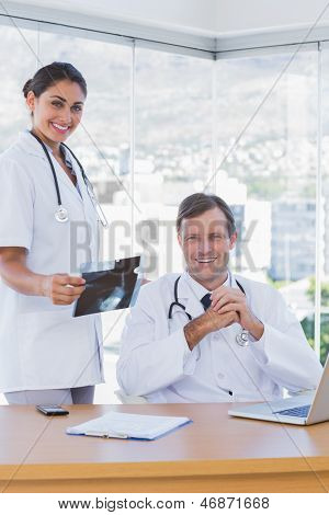 Cheerful group of doctors working on a x ray in a modern office