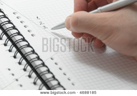 Hand Writing Simple Numbered List On White Spiral Notebook With Elegant Silver Pen