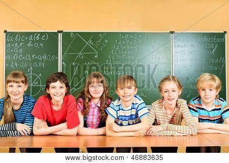 Group of school children studying in classroom.