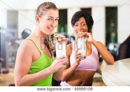 Young People - women in the gym drinking a isotonic drink or protein shake