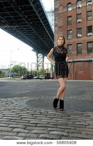 Woman wearing black minidress standing under Manhattan Bridge