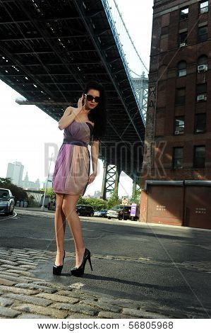 Young brunette model standing under Manhattan Bridge