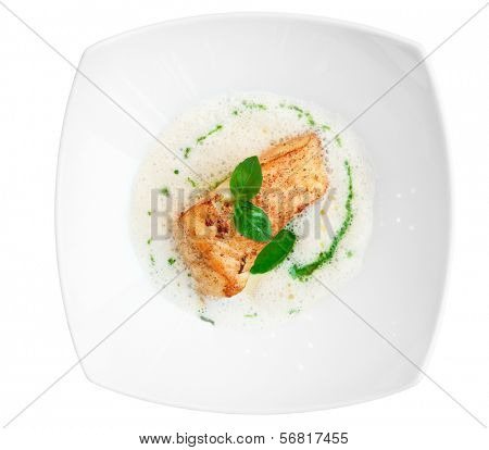 Braised fish fillet with froth sauce shot from above isolated on white