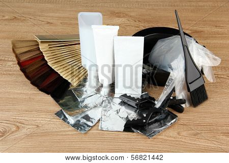 Hair dye kit and hair samples of different colors, on wooden background