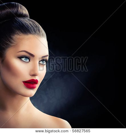 Fashion Model Girl Portrait with Blue Eyes and Full Sexy Red Lips. Creative Hairstyle. Hair Bun. Hairdo. Make up. Beauty Woman isolated on a Black Background
