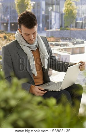 Young man sitting in citypark, using laptop computer, inserting USB flash drive.