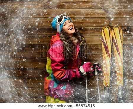 Smiling woman with skies standing against wooden house wall  in a snow
