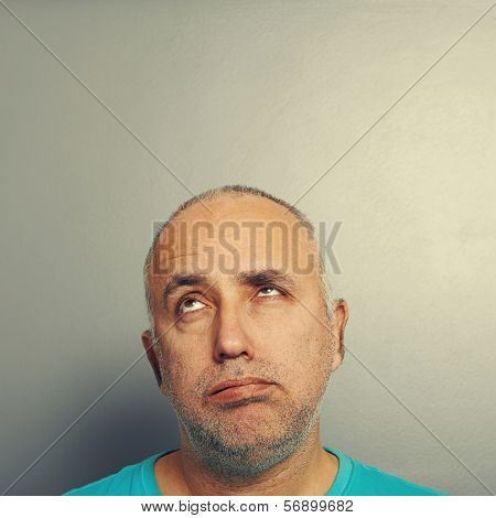 portrait of bored senior man looking up over grey background