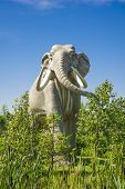 Sculpture of prehistoric elephant living in forest. poster