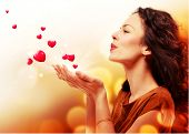 Beauty Young Woman Blowing Hearts from her Hands. St. Valentines Day Concept. Beautiful Girl in Love. Valentine art design. Valentines Gift poster