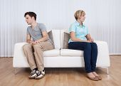 Brother and sister have had an argument and are sitting at opposite ends of a sofa poster