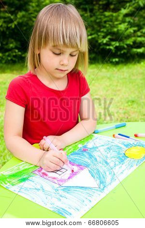 Little girl sitting at table drawing a house outdoors
