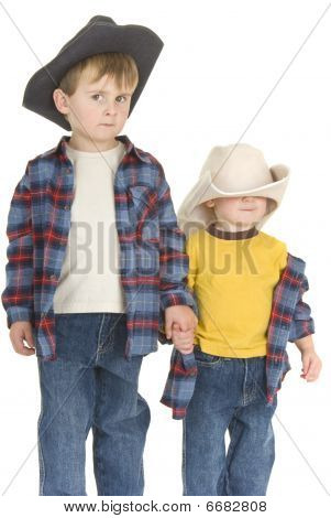 A suspicious older cowboy brother holds little brother's hand