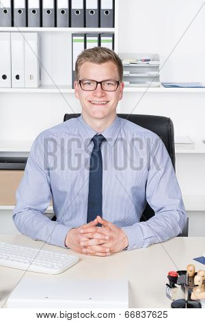Young Businessman Is Sitting At The Desk