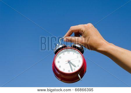 Hand Hold Chrome Alarmclock On Blue Sky Abckground