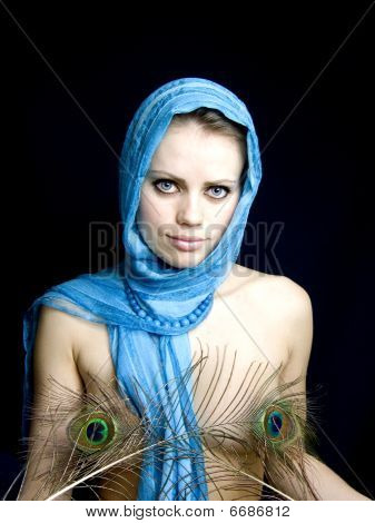 Beautiful Girl In A Scarf And With A Feather In A Hand