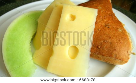 Bread, slice of honeydew melon and cheese on a plate