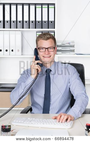 Man Is Phoning And Typing At The Keyboard