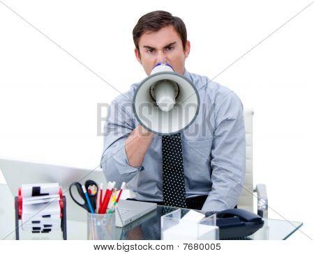 Furious Businessman Yelling Through A Megaphone Sitting At His Desk