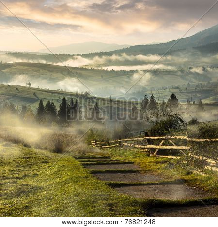 Steps Down To Village In Foggy Mountains At Sunrise