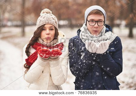 Portrait of cute young dates in casual winterwear blowing snowflakes from palms