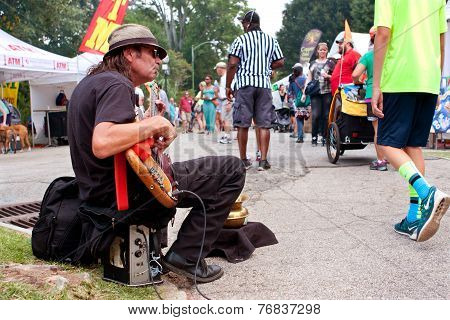 Man Strums Bass Guitar For Tips At Arts Festival