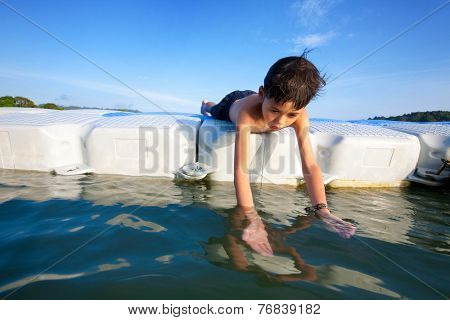 Young boy lying on floating platform in sea trying to catch small prawn